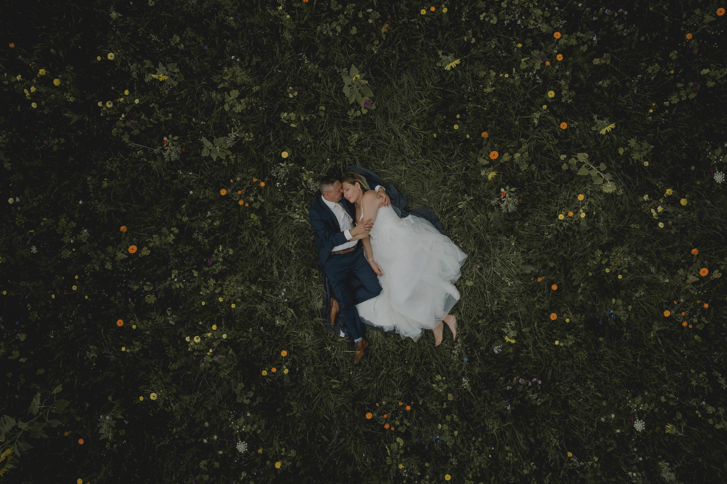 Hochzeitsfotograf Leipzig - Brautpaar liegend auf einer Blumenwiese
