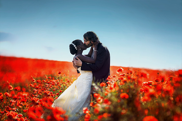 Küßendes Brautpaar im Mohnfeld