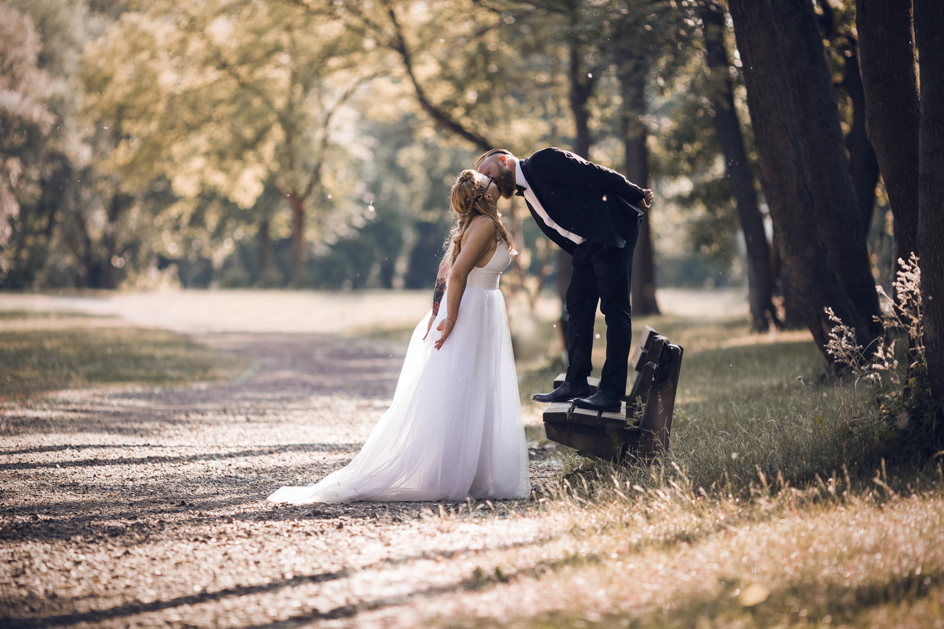 Hochzeitsfotogaf Leipzig - Küßendes Brautpaar an der Promenade an der Saale
