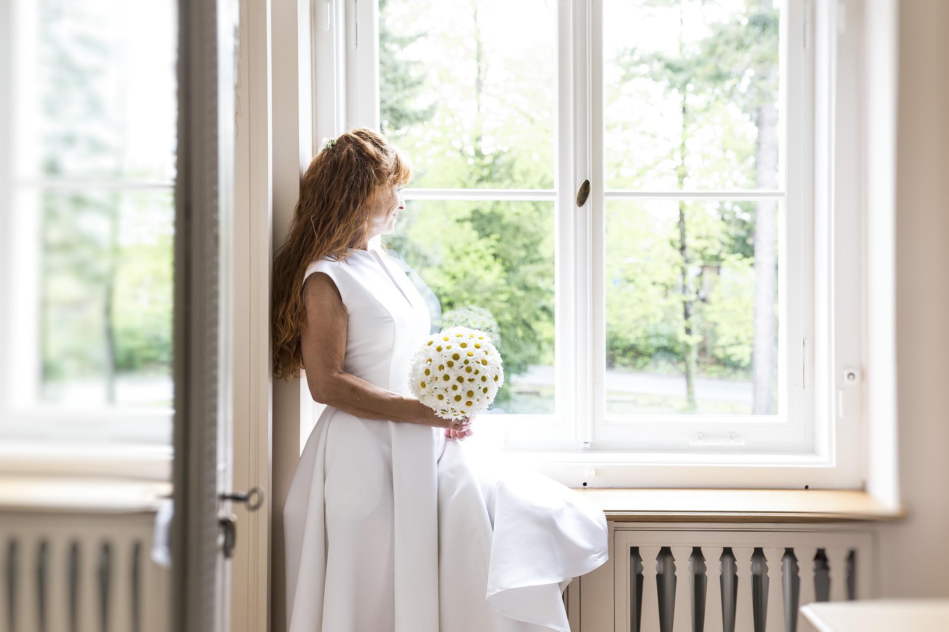 Hochzeitsfotogaf Leipzig - Braut blickt sehnsüchtig aus dem Fenster