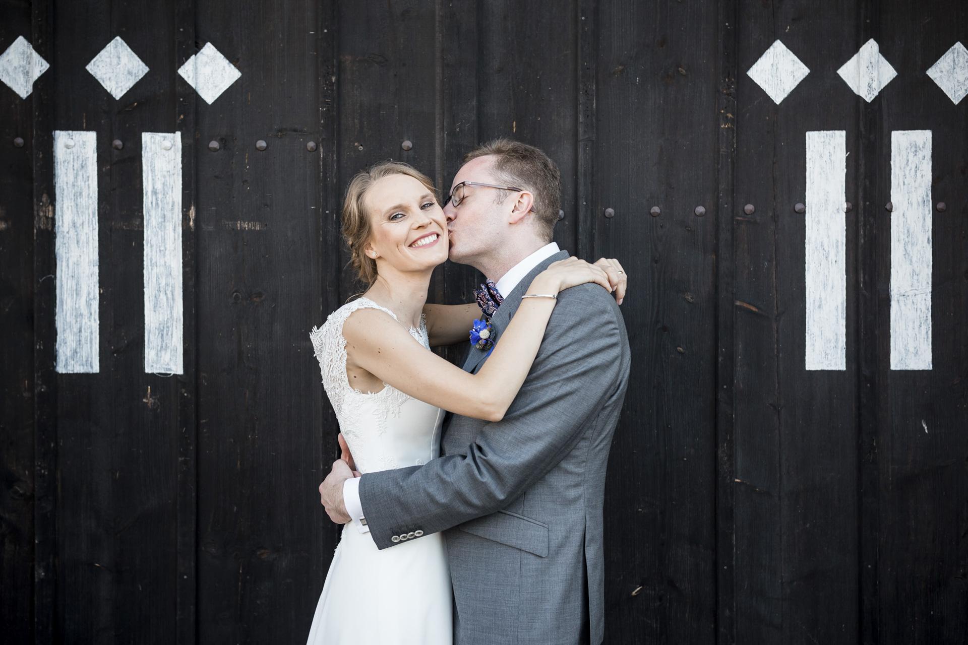 Hochzeitsfotogaf Leipzig - Brautpaar küßend vor dem Hoftor der Denkmalschmiede
