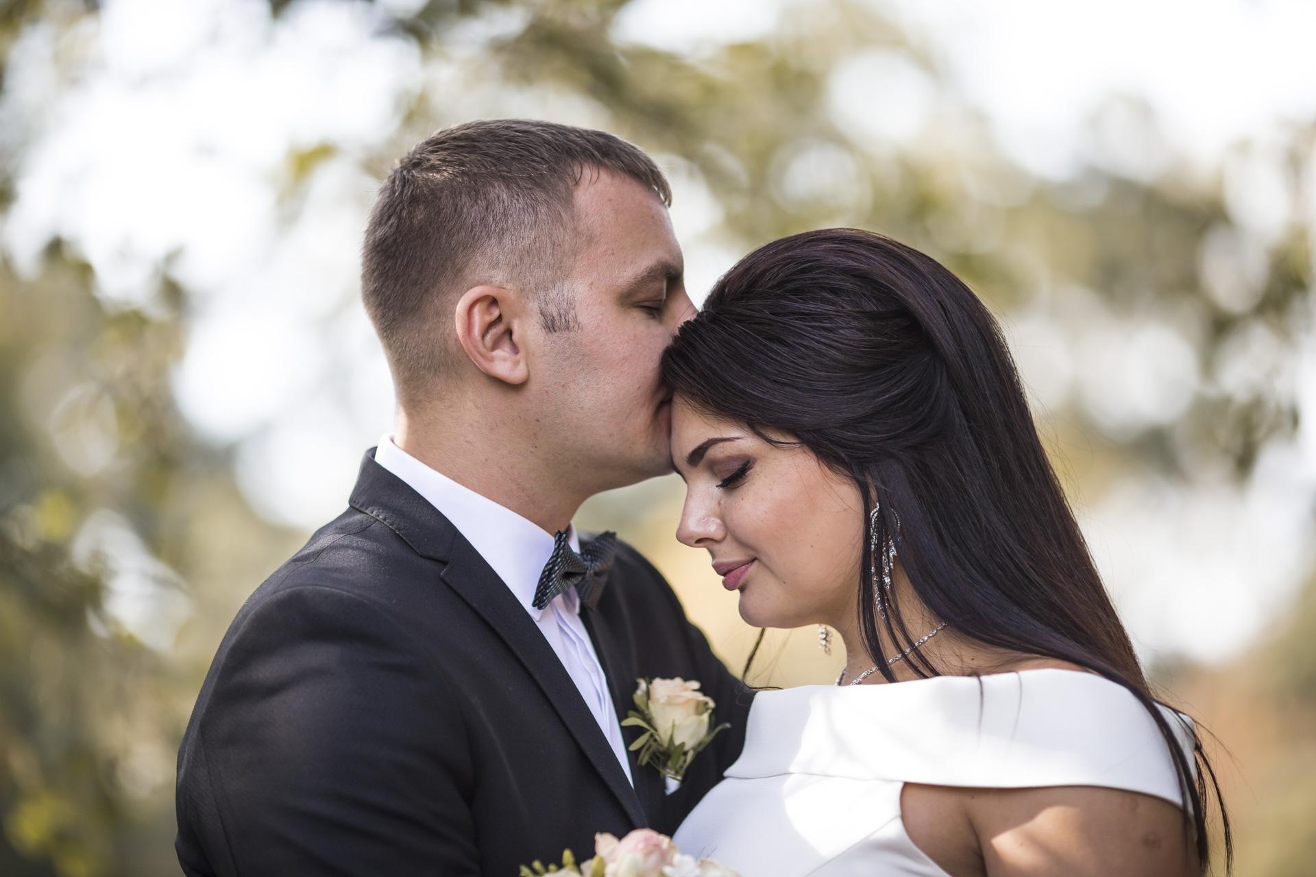 Hochzeitsfotogaf Leipzig - Bräutigam küßt die Stirn seiner Braut