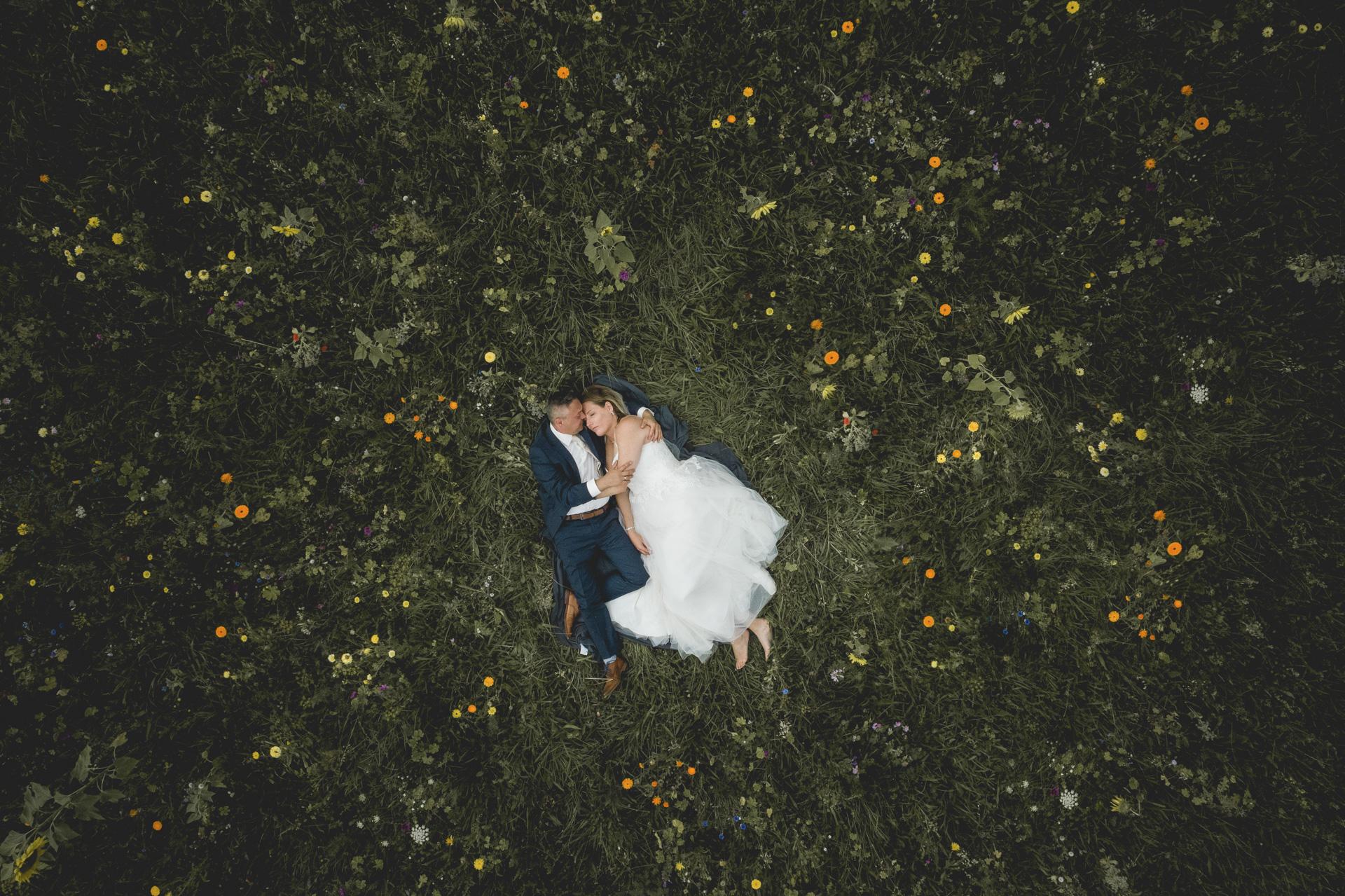 Hochzeitsfotogaf Leipzig - Brautpaar liegend auf einer grünen Wiese mit vielen Wildblumen